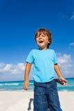 Happy boy stands on sandy beach of ocean coast Royalty Free Stock Photos