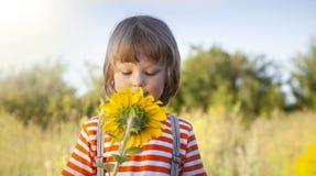 Happy boy with sunflower outdoors. Children play in garden