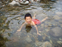 Happy Boy Swimming in the Creek Stock Photography