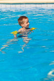 Happy boy swimming with floaties Stock Photography