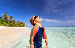 Happy boy in swimming goggles on beach Stock Photo