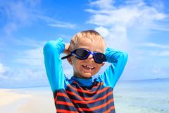 Happy boy in swimming goggles at the beach Stock Images