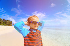 Happy boy in swimming goggles on beach Stock Images
