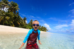 Happy boy in swimming goggles on beach Stock Photos