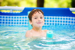 Happy boy in a swimming pool. Smiling child in an outdoor pool on a hot summer day Royalty Free Stock Photography