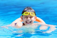 Happy boy on the swimming pool, summertime. Happy boy at the swimming pool with swimming goggles on head , floating with swim noodles on a summer day Stock Photography