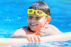 Happy boy on the swimming pool, summertime. Happy boy at the swimming pool with swimming goggles on head , floating with swim noodles on a summer day Stock Image