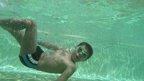 Boy swimming under water. Happy boy swimming under water stock video