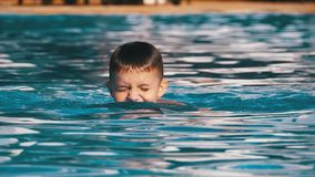 Happy boy swims in a pool with blue water. Slow motion. In 180 fps. the child fun floundering in the clear, transparent water of the pool by the exotic hotel stock footage