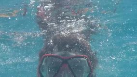 Happy boy swims underwater in swimming pool with snorkel mask. Guy in the underwater mask stock video