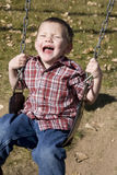 Happy boy swinging Royalty Free Stock Image