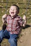 Happy boy swinging Royalty Free Stock Image