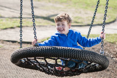 Happy Boy Swinging on a Big Round Swing Royalty Free Stock Photography