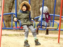 Happy boy swinging on the playground Stock Photography