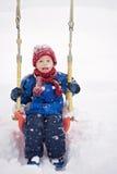Happy boy swinging in winter park Stock Photography