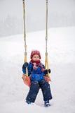 Happy boy swinging in winter park Royalty Free Stock Photos