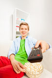 Happy boy switches remote control holding popcorn Stock Images