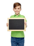 Happy boy in t-shirt holding blank chalk board Royalty Free Stock Photography
