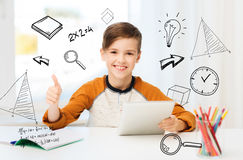 Happy boy with tablet pc showing thumbs up at home Royalty Free Stock Photo