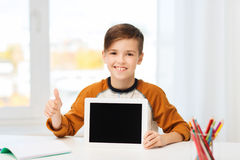 Happy boy with tablet pc showing thumbs up at home Stock Photo
