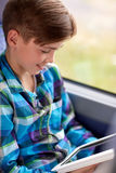 Happy boy with tablet pc in travel bus or train. Transport, tourism, road trip, technology and people concept - happy boy with tablet pc computer in travel bus Royalty Free Stock Images