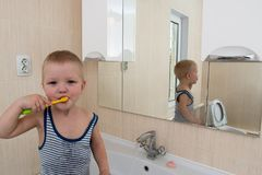 Happy boy taking bath in kitchen sink. Child playing with foam and soap bubbles in sunny bathroom with window. Little baby bathing. Water fun for kids. Hygiene stock photography