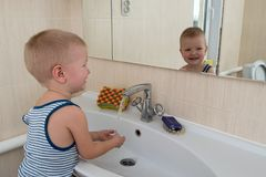 Happy boy taking bath in kitchen sink. Child playing with foam and soap bubbles in sunny bathroom with window. Little baby bathing. Water fun for kids. Hygiene royalty free stock photo