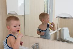 Happy boy taking bath in kitchen sink. Child playing with foam and soap bubbles in sunny bathroom with window. Little baby bathing. Water fun for kids. Hygiene royalty free stock photos