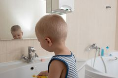 Happy boy taking bath in kitchen sink. Child playing with foam and soap bubbles in sunny bathroom with window. Little baby bathing. Water fun for kids. Hygiene stock photo