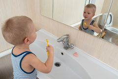 Happy boy taking bath in kitchen sink. Child playing with foam and soap bubbles in sunny bathroom with window. Little baby bathing. Water fun for kids. Hygiene stock images