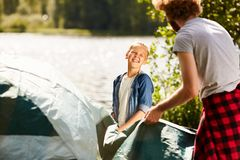 Tent by waterside. Happy boy talking to his father while helping him to prepare tent by waterside in natural environment Royalty Free Stock Photography