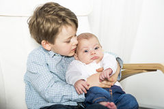 Happy boy talking to his newborn baby sister. A Happy boy talking to his newborn baby sister Stock Photography