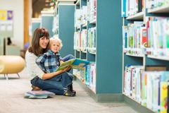 Happy Boy And Teacher Reading Book In Library Royalty Free Stock Images