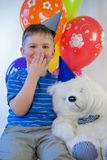 Happy boy with a teddy bear in the party. Boy presented with a birthday teddy bear Royalty Free Stock Photos