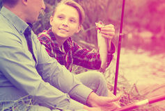 Happy boy teenager and father fishing together Royalty Free Stock Photography