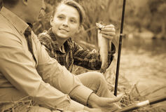 Happy boy teenager and father fishing together Stock Images