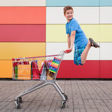 Boy with shopping trolley. The happy boy the teenager joyfully jumps near to the cart full of purchases stock photo