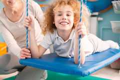 Happy boy on therapy swing. Happy little boy laying on therapy swing Royalty Free Stock Photos