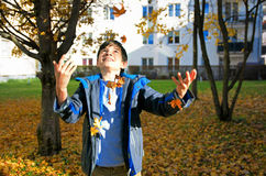 Happy boy throwing autumn leaves Royalty Free Stock Images
