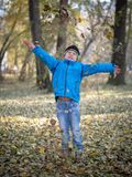 Happy boy throws leaves in autumn Park stock photo