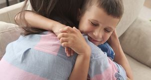 Boy tightly embracing his mother. Happy boy tightly embracing his mother at home stock video footage