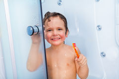 Happy boy with toothbrush showering in the cabin Royalty Free Stock Image
