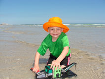 Happy Boy with Toy Crane on Beach. Smiling young boy playing on a beach with a toy truck crane in a bright orange hat Royalty Free Stock Photo