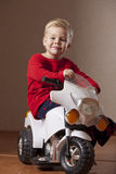 Happy Boy on Toy Motorcycle Royalty Free Stock Image