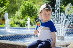 Happy boy of two years is sitting near the fountain in the summe Royalty Free Stock Images