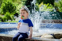 Happy boy of two years is sitting near the fountain in the summe Royalty Free Stock Photo