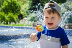 Happy boy of two years is sitting near the fountain in the summe Royalty Free Stock Image