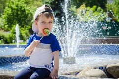 Happy boy of two years is sitting near the fountain in the summe Royalty Free Stock Photos