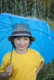 Happy boy with umbrella outdoors, child with an umbrella walks in rain. Happy boy with umbrella outdoors, child with an umbrella walks in the rain stock photo