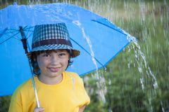 Happy boy with umbrella outdoors, child with an umbrella walks in rain. Happy boy with umbrella outdoors, child with an umbrella walks in the rain stock photography